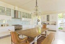 Lampadario sopra il tavolo in legno in cucina — Foto stock