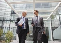 Businessmen walking out of office building together — Stock Photo