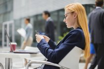 Businesswoman using cell phone at table outside — Stock Photo