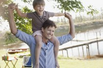 Father carrying smiling son on shoulders at lakeside — Stockfoto