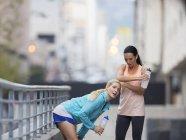 Mujeres descansando después de hacer ejercicio en la calle de la ciudad - foto de stock