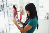 Woman examining perfume in drugstore — Stock Photo