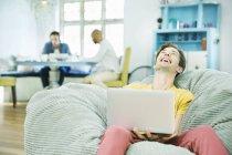 Смеющийся человек, используя ноутбук в кресле погремушка — стоковое фото
