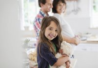 Girl holding teddy bear in kitchen — Stock Photo