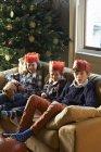 Bambini felici in corone di carta che si siede sul divano — Foto stock