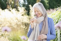 Older woman smelling flowers outdoors — Stock Photo