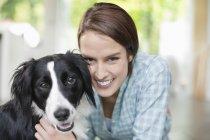 Lächelnde Frau streichelt Hund im modernen Zuhause, Nahaufnahme — Stockfoto