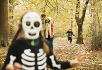 Children in skeleton costumes playing in park — Stock Photo