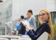 Donna di affari che lavorano al tavolo all'esterno di edificio per uffici — Foto stock