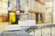 Envases en cinta transportadora en almacén - foto de stock