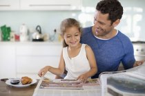 Father and daughter reading newspaper at breakfast — Stockfoto