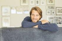 Молодий привабливою усміхнений чоловік, сидячи на дивані — стокове фото