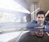 Businessman resting on car in parking garage — Stock Photo