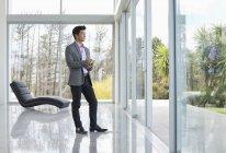 Geschäftsmann steht am modernen Bürofenster — Stockfoto