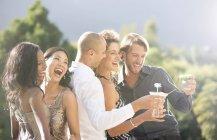 Joven atractivo amigos riéndose juntos de fiesta - foto de stock