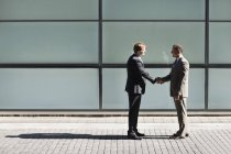 Businessmen shaking hands outdoors of modern office — Stock Photo