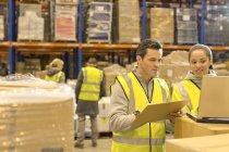 Travailleurs qui utilisent l'ordinateur portable dans l'entrepôt — Photo de stock