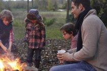 Батько і діти, сидячи навколо багаття на природі — стокове фото