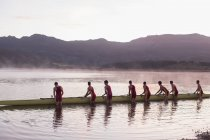 Академическая гребля экипажа, поместив череп в озеро на рассвете — стоковое фото