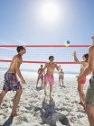 Happy caucasian friends playing beach volleyball — Stock Photo