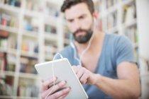 Закрыть человека, слушающего музыку на цифровом планшете — стоковое фото