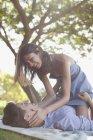 Ласкавим пара на ковдру в траві під дерево — стокове фото