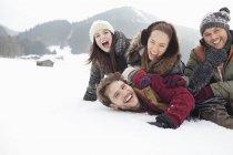 Amis ludiques portant sur terrain enneigé — Photo de stock