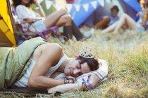Людина в tiara спати в спальний мішок за межами намети на фестивалі музики — стокове фото