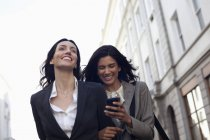 Happy businesswomen text messaging with cell phone — Stockfoto