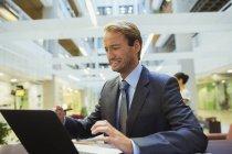 Homme d'affaires inquiets lors de l'utilisation d'ordinateur portable dans l'immeuble de bureaux moderne — Photo de stock