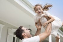 Father and daughter playing outside house — Stock Photo