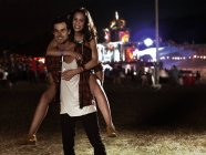 Portrait of man piggybacking woman at music festival — Stock Photo