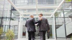 Заднього вигляду бізнесменів ходьбі в офісної будівлі разом — стокове фото