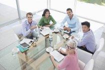 Деловые люди улыбаются на встрече в современном офисе — стоковое фото