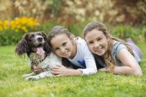 Filles souriantes relaxant avec chien sur la pelouse — Photo de stock
