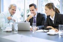 La gente d'affari che condivide il computer portatile in riunione a ufficio moderno — Foto stock