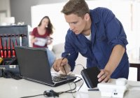Skillful caucasian electrician using laptop in home — Stock Photo
