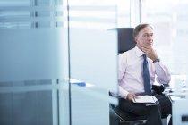 Бизнесмен думает за столом в современном офисе — стоковое фото