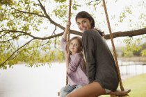 Portrait of mother and daughter on swing at lakeside — Stock Photo