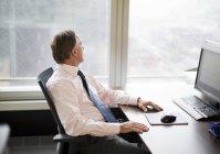 Hombre de negocios mirando por la ventana en la oficina moderna - foto de stock