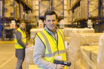 Worker scanning boxes in warehouse — Stock Photo