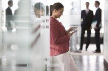Бізнес-леді за допомогою цифровий планшетний в коридорі сучасні офісні — стокове фото
