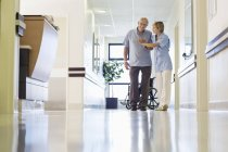 Krankenschwester hilft Patientin beim Gang in Krankenhausflur — Stockfoto