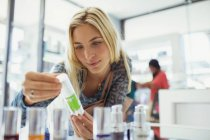 Woman examining skincare product in drugstore — Stockfoto