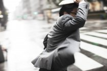 Businessman crossing city street — Stock Photo