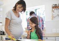 Вагітна мати дочка допомоги з домашнє завдання — стокове фото
