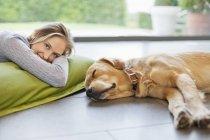Femme souriante relaxant avec chien sur le sol à la maison moderne — Photo de stock