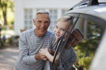 Older man talking to granddaughter in car window — Stock Photo