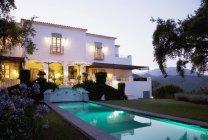 Luxury lap pool and villa at dusk — Stock Photo