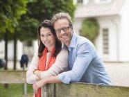 Пара посміхаючись дерев'яний паркан — стокове фото